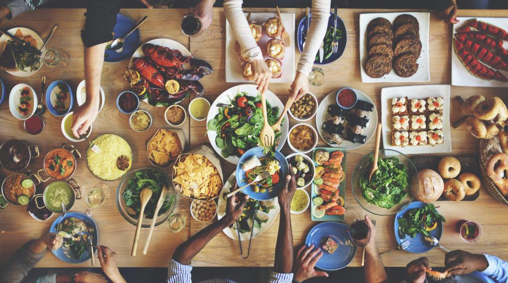 Crowd enjoying a full table of healthy food